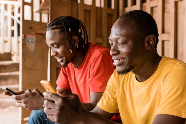 Hommes smiley coup moyen avec smartphones