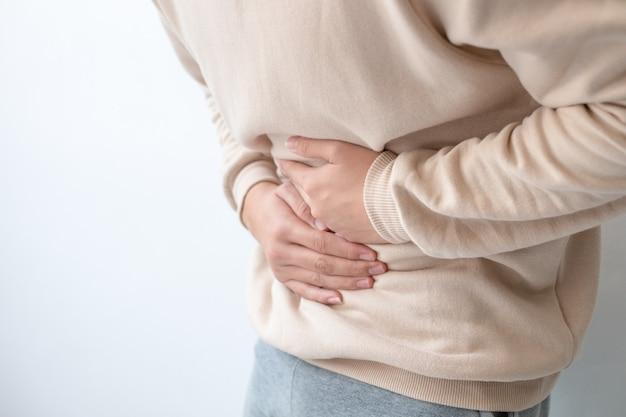Hommes souffrant de douleurs abdominales debout, tenant le corps et les mains photos