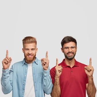 Hommes souriants positifs avec des barbes épaisses, des coupes de cheveux à la mode