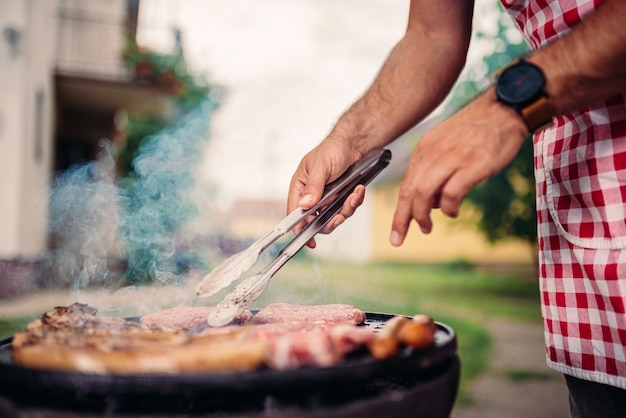 Hommes, tablier, barbecue, viande poulet