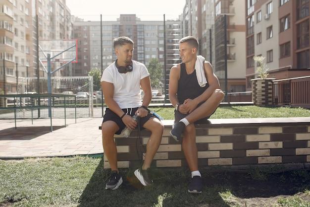 Les hommes en tenue de sport se reposent après une formation dans un parc
