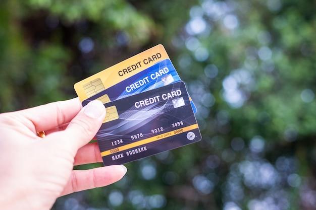 Les hommes tiennent la carte de crédit sur la nature de bokeh