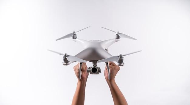 Les hommes tiennent le drone décollent avec la caméra sur le fond blanc, isolé.