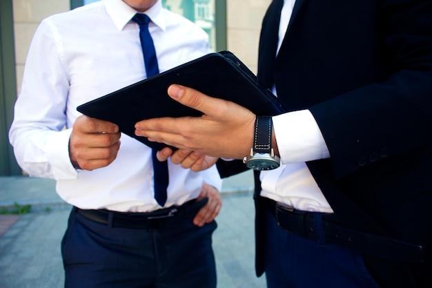 Les hommes tiennent une tablette