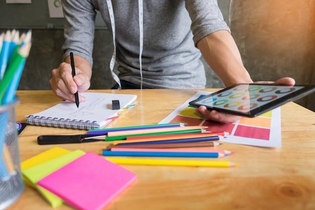 Hommes travaillant comme créateur de mode choisissant sur le tableau de couleur pour les vêtements dans une tablette numérique au studio en milieu de travail.