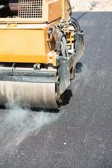 Hommes travaillant sur une nouvelle rue en mettant un nouvel asphalte