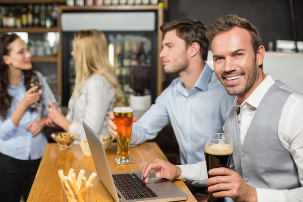 Hommes travaillant sur un ordinateur portable pendant que les femmes parlent derrière
