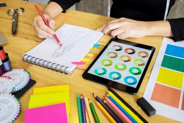 Hommes travaillant en tant que styliste en choisissant sur la charte de couleurs pour les vêtements en tablette numérique au studio de travail.