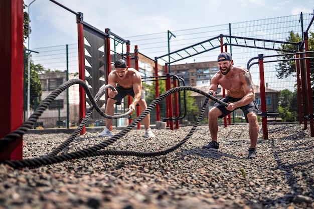 Les hommes travaillent dur avec une corde à la cour de gym de rue. entraînement en plein air. concept de remise en forme, sport, exercice, formation et mode de vie.