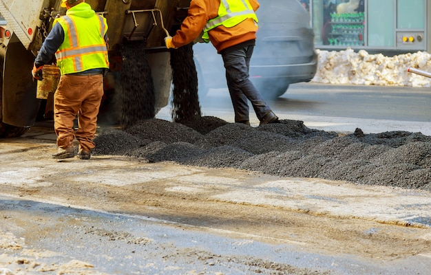 Les hommes travaillent dur route asphaltée avec des pelles