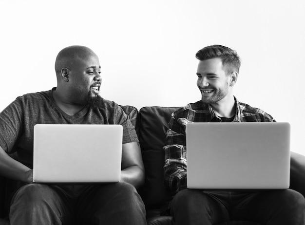 Hommes utilisant un ordinateur portable assis sur un canapé