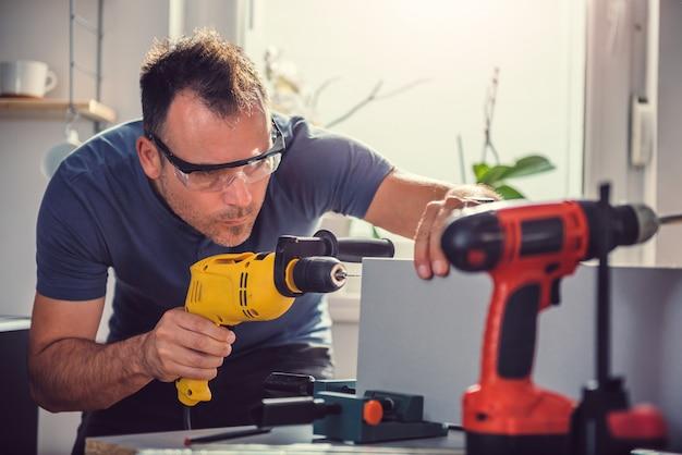 Hommes utilisant une perceuse électrique