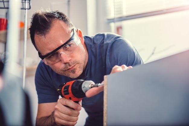 Hommes utilisant une perceuse sans fil