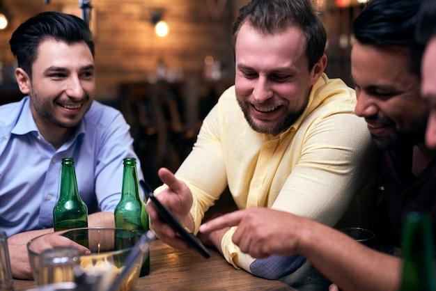 Hommes utilisant un téléphone portable lors d'une réunion au pub