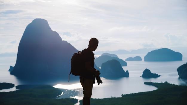 Les hommes voyagent en photographie sur la montagne. touriste en vacances d'été. paysage belle montagne sur mer au point de vue de samet nangshe. baie de phang nga, voyage en thaïlande, nature d'aventure de voyage.