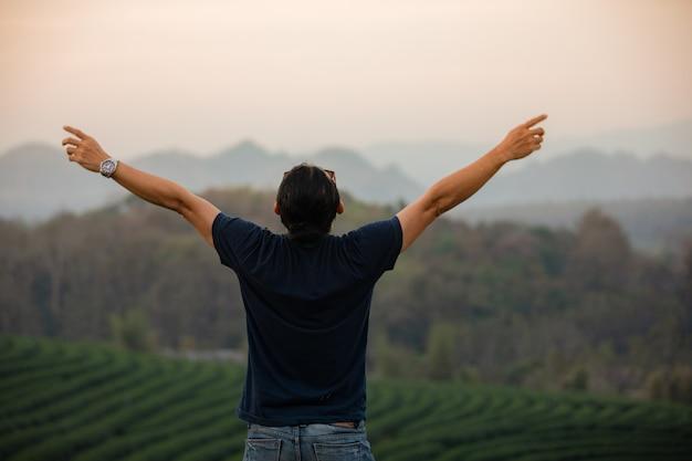 Hommes de voyageur de liberté debout avec les bras levés et profitant d'une belle nature