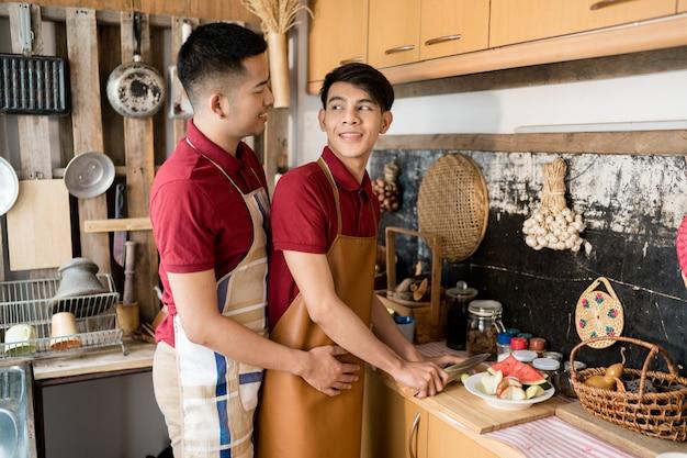 Un homosexuel lgbt boit du café et aide à cuire des aliments dans la cuisine.