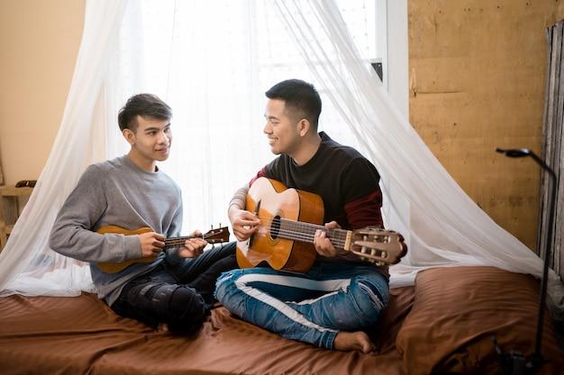 Homosexuel lgbt s'amusant à jouer de la guitare ensemble.