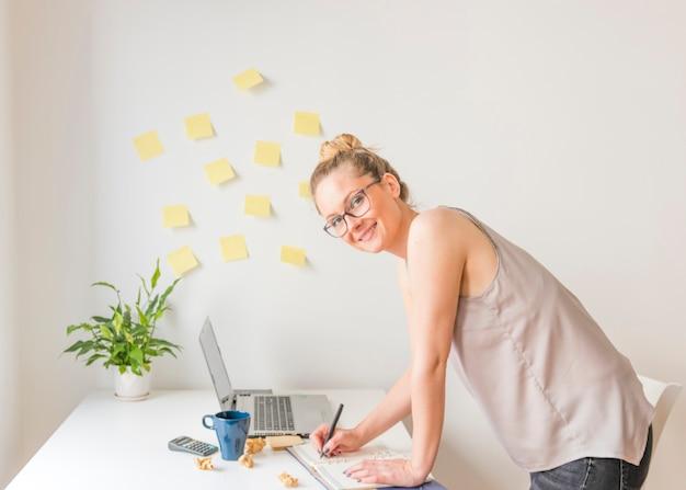 Horaire d'écriture de femme d'affaires heureux dans le journal