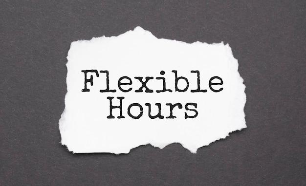 Horaires flexibles signe sur le papier déchiré sur fond noir