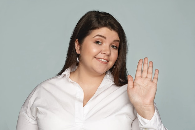 Horizontal amical à la recherche élégante jeune femme de taille plus avec un sourire joyeux agitant la main, disant bonjour à vous. émotions, signes, gestes et langage corporel positifs