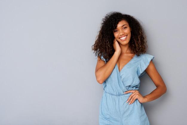 Horizontale belle jeune femme noire souriant sur fond gris