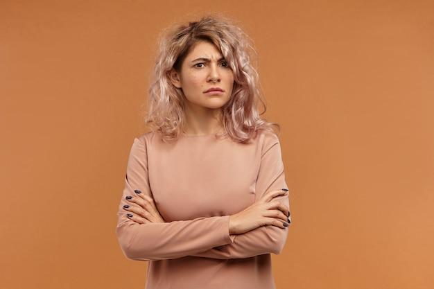 L'horizontale de la jeune femme européenne têtue frustrée avec piercing facial et coiffure élégante en fronçant les sourcils, gardant les bras croisés sur sa poitrine,