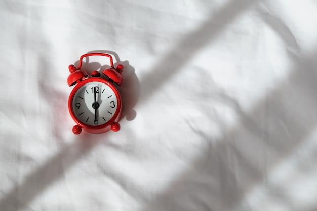 Horloge analogique rouge sur des feuilles froissées blanches. vue de dessus, mise à plat, espace de copie. horizontal.