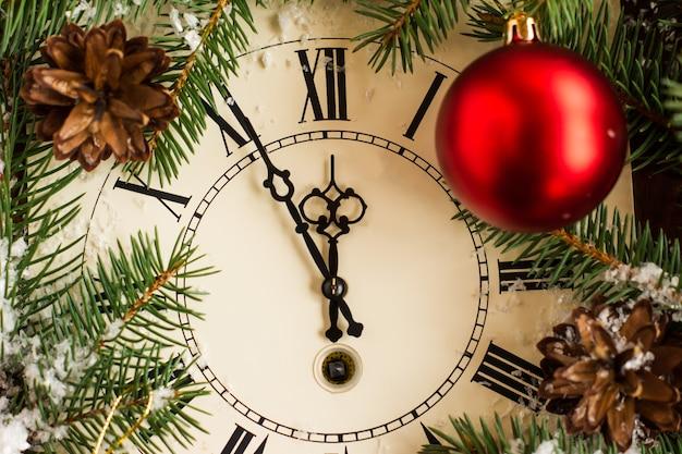 Une horloge ancienne pour le réveillon ou la nuit de noël avec un compte à rebours jusqu'à minuit dans une décoration festive.