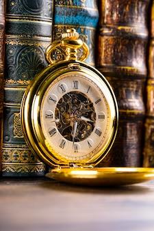 Horloge antique sur fond de livres vintage. mouvement mécanique sur chaîne.