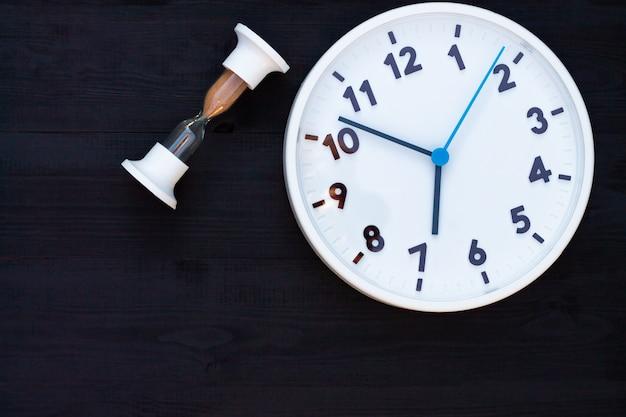 Horloge blanche et sablier sur un fond en bois noir. vue de dessus. espace de copie. concept d'éducation ou d'entreprise.