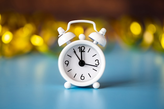 Horloge blanche vue de face sur fond doré flou