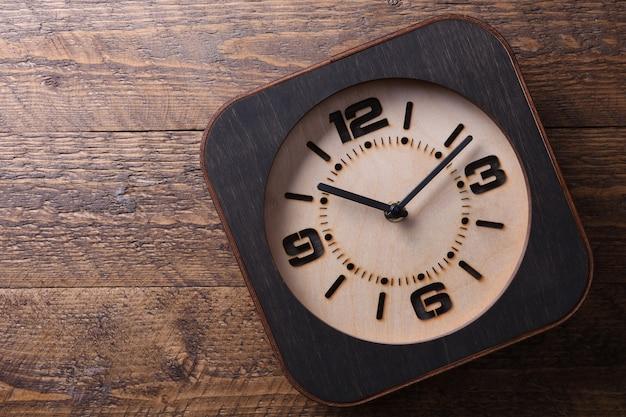 Horloge en bois faite à la main sur une table en bois. fermer.