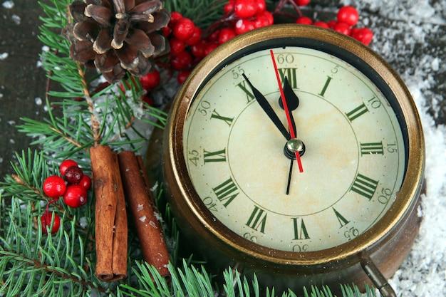 Horloge avec des branches de sapin et des baies sur la neige sur une table en bois
