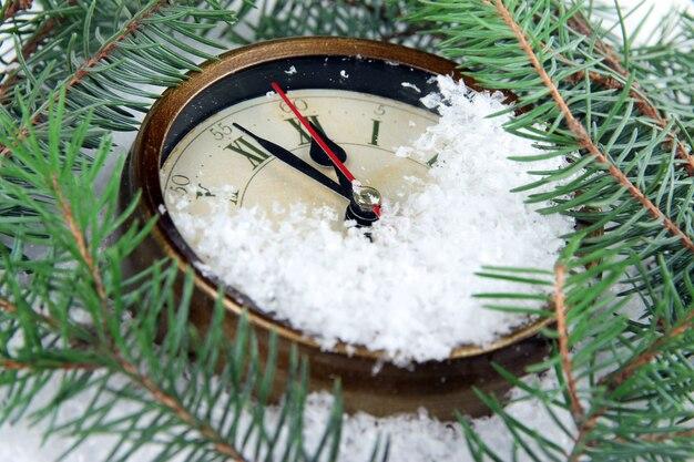 Horloge et branches de sapin sous la neige se bouchent