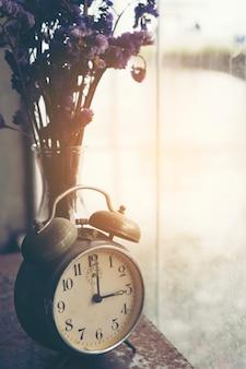 Horloge de bureau avec fleurs séchées, image de filtre vintage