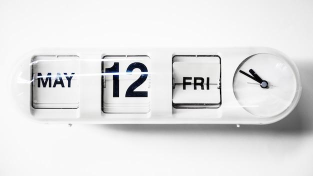 Horloge avec calendrier à date isolé sur blanc
