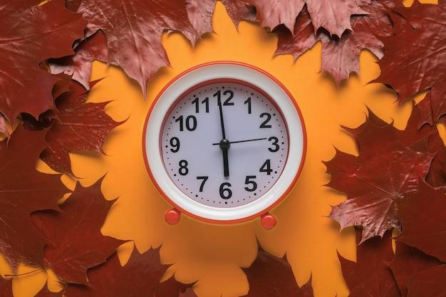 Horloge classique avec des mains sur fond orange avec des feuilles d'automne.