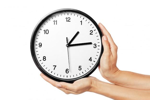 Horloge dans les mains isolé sur blanc