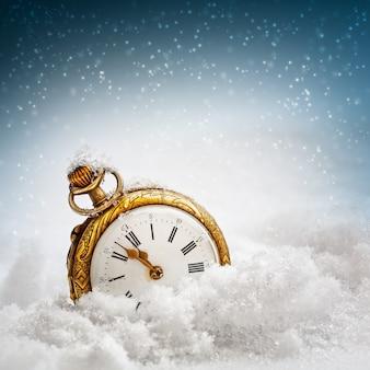 Horloge du nouvel an avant minuit. montre de poche antique dans la neige