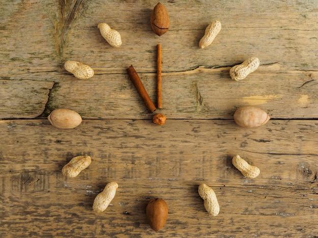 Horloge faite de différentes noix et cannelle sur table en bois