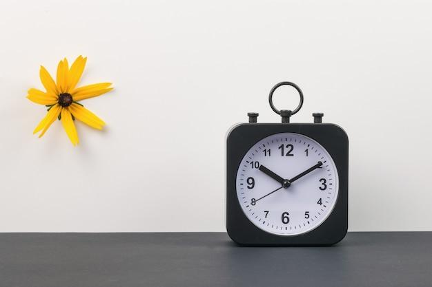Une horloge et une fleur orange sur fond noir et blanc.
