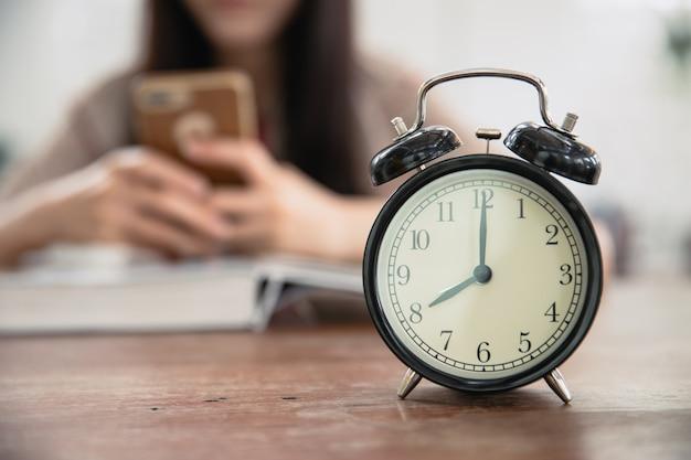Horloge avec flou adolescente jouant smartphone en lisant un livre pour perdre du temps