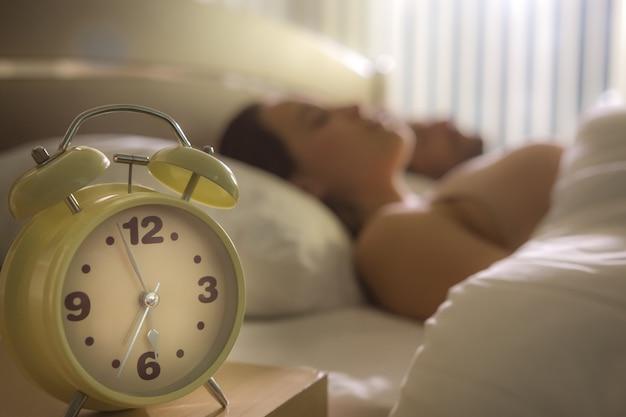 L'horloge sur le fond du couple dans le lit