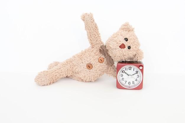 L'horloge et un joli ours en peluche montrent une pose de yoga simple pour s'étirer et se renforcer.