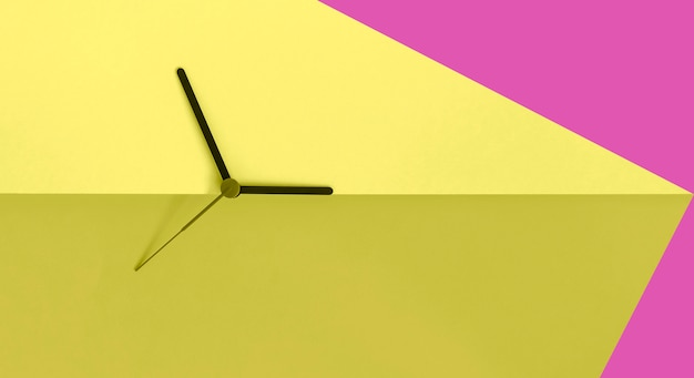 Horloge mains sur fond de bloc de couleur rose et jaune acide. concept de l'heure d'été. changement d'heure saisonnier. concept de temps. copiez l'espace.
