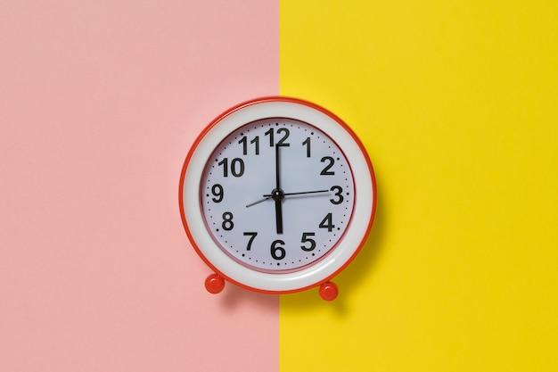 Horloge avec des mains sur un fond jaune et rose. horloge analogique classique.