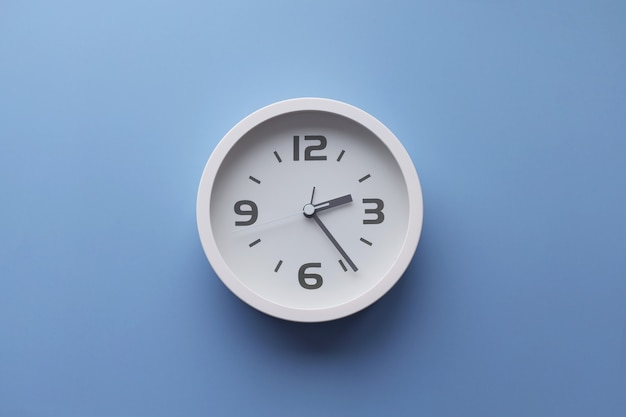 Horloge murale blanche sur le mur. image minimaliste à plat d'une horloge murale en plastique sur fond bleu turquoise avec espace de copie et composition centrale.