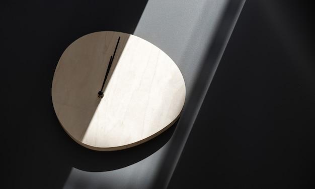 Horloge murale en bois accrochée à un mur gris dans un rayon de soleil.