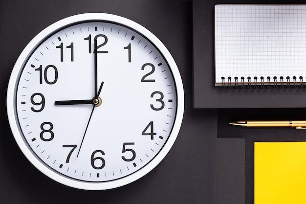 Horloge murale et cahier vérifié sur fond de papier noir abstrait